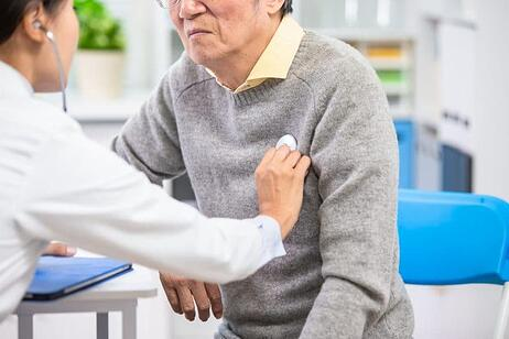 Female doctor uses a stethoscope to examine an elderly paient's heartbeat