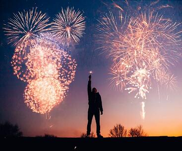 Man with a firework in his hand while fireworks are exploding in the air